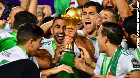 Algeria's forward Riyad Mahrez and his teammates celebrate with the trophy after winning the 2019 Africa Cup of Nations (CAN) Final football match between Senegal and Algeria at the Cairo International Stadium in Cairo on July 19, 2019. (Photo by Giuseppe CACACE / AFP)        (Photo credit should read GIUSEPPE CACACE/AFP/Getty Images)