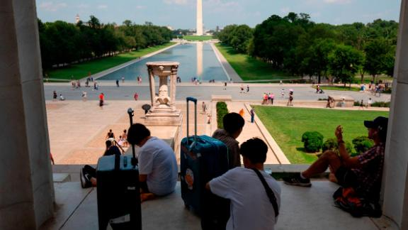 People rest in the shade at the Lincoln Memorial on the National Mall in Washington, DC, on July 19.