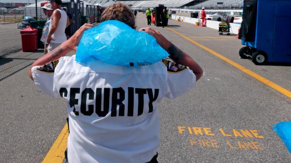 Track security officer Patty Patterson carries a bag of ice on her shoulders as she walks back to her post during a NASCAR Cup Series auto race practice at New Hampshire Motor Speedway in Loudon, New Hampshire, on July 20.