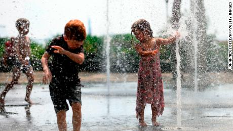 Children cool down as they play in a public fountain during summer heat in New York City.