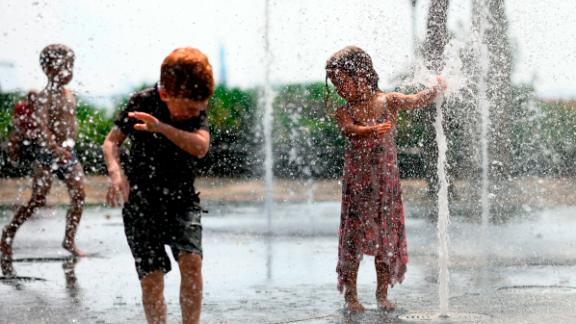 Children cool down as they play in a public fountain in New York on July 19.
