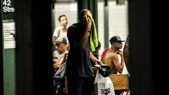 A man wipes his face with a towel while standing on subway platform in New York on July 20.