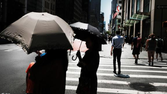 People hold umbrellas to shade themselves from the sun on July 19, in New York.