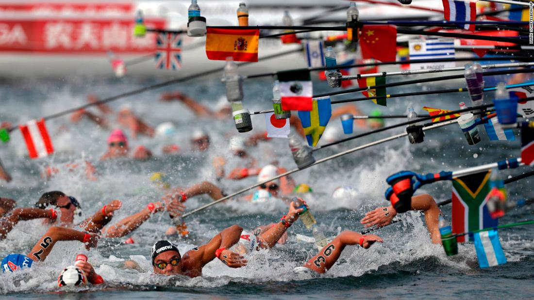 Swimmers reach for water bottles while competing in the men's 10km open water swim at the World Swimming Championships in Yeosu, South Korea, on Tuesday, July 16.