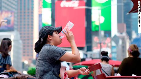 A woman drinks water in Times Square as temperatures reach the mid-to-upper 90s Saturday, July 20, 2019, in New York.  Americans from Texas to Maine sweated out a steamy Saturday as a heat wave spurred cancelations of events from festivals to horse races and the nation's biggest city ordered steps to save power to stave off potential problems.   (AP Photo/Jonathan Carroll)