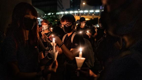 Mourners hold candles during a candlelight vigil to commemorate a protestor who died last night during a rally against a controversial extradition law proposal on June 17, 2019 in Hong Kong, China.