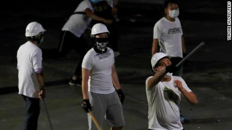 Men in white T-shirts with poles are seen in Yuen Long after attacking anti-extradition bill demonstrators at a train station, in Hong Kong, China July 22, 2019. REUTERS/Tyrone Siu