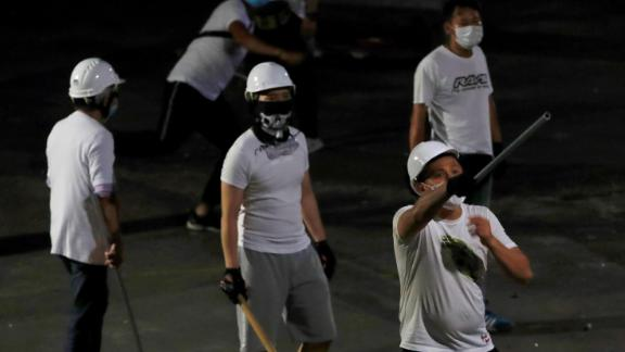 Masked men in white T-shirts are seen after attacking anti-extradition bill demonstrators at a train station in Yuen Long.