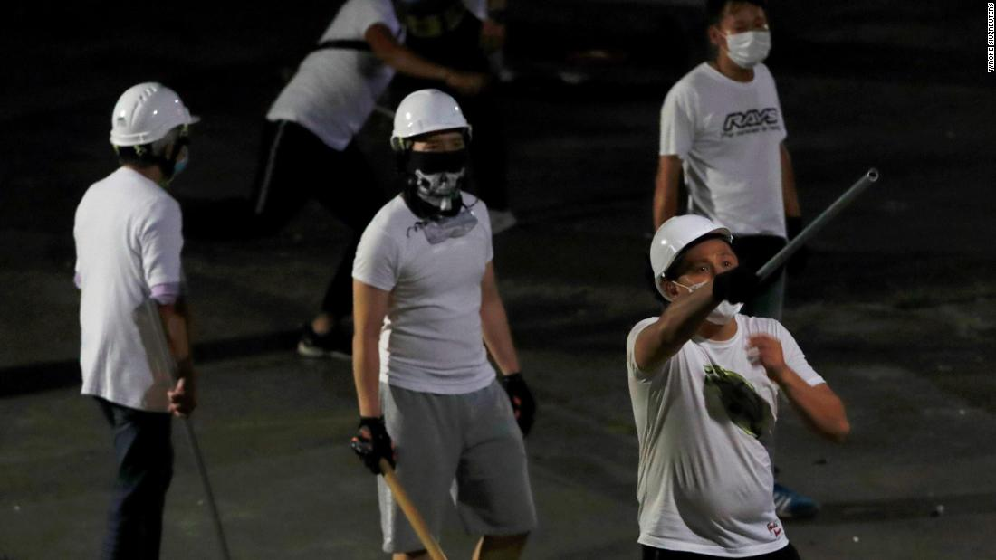 Masked men in white t-shirts with poles are seen after attacking anti-extradition bill demonstrators at a train station in Yuen Long, early on July 22.