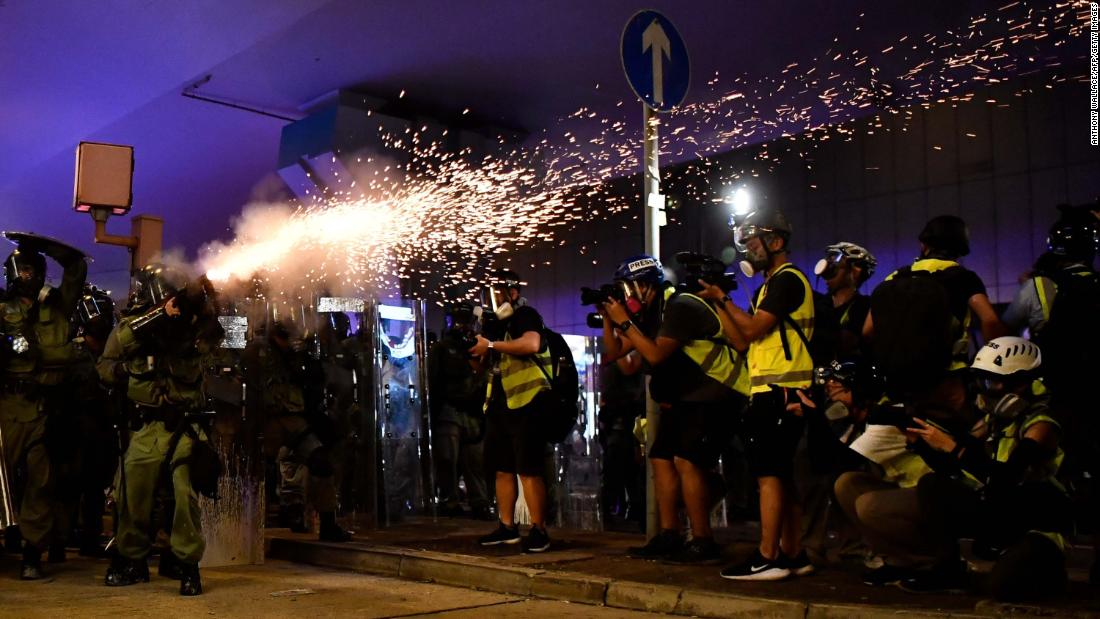 A policeman fires tear gas to disperse protesters.