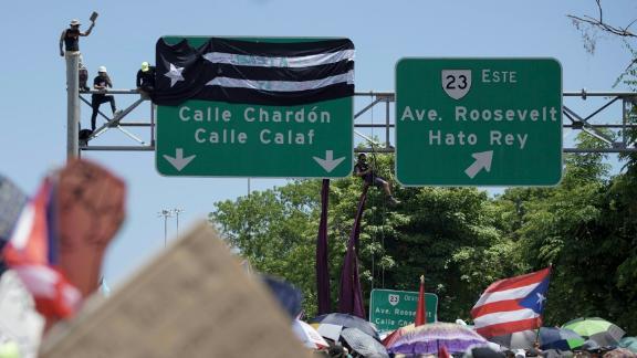 Protesters attach a banner to a highway sign.