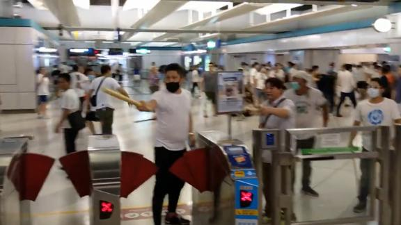 A mob attacks commuters in Hong Kong.