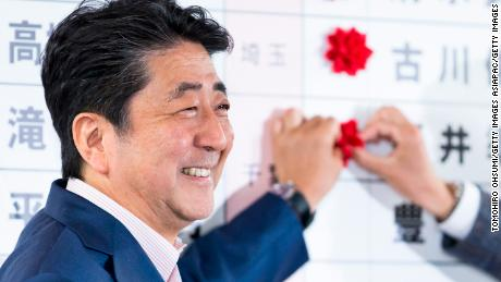 Japanese Prime Minister and ruling Liberal Democratic Party (LDP) President Shinzo Abe places a red paper rose on a LDP candidate's name to indicate an upper house election victory on July 21, 2019 in Tokyo, Japan.
