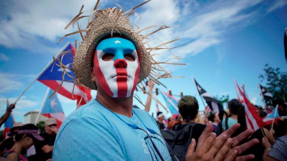 A masked man protests in San Juan.