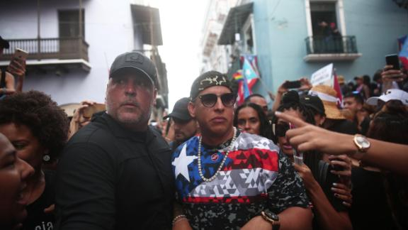 Singer Daddy Yankee, in the flag shirt, attends the rally on Monday.