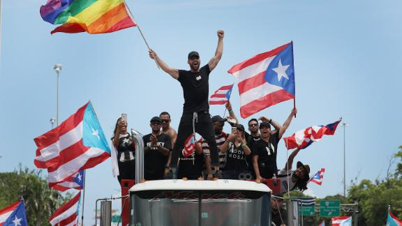 Puerto Rican pop star Ricky Martin, waving a rainbow flag, joins the protests on Monday. Members of the group chat that Rosselló took part in made vulgar references to the star's sexuality.