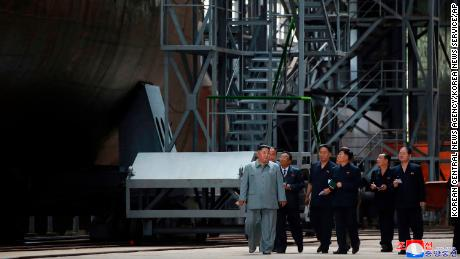 North Korean leader Kim Jong Un is seen standing beside a submarine under construction in this photograph released by North Korean state media Tuesday.