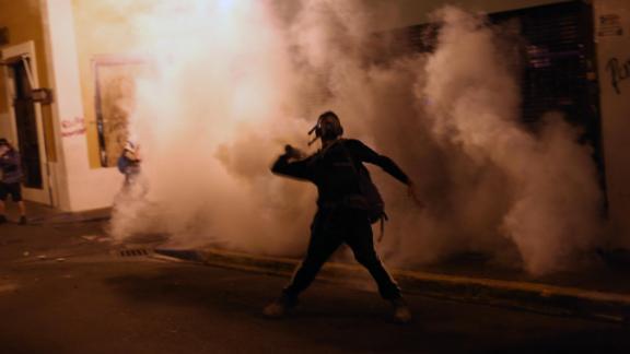 A protester throws a tear gas canister toward police in San Juan.
