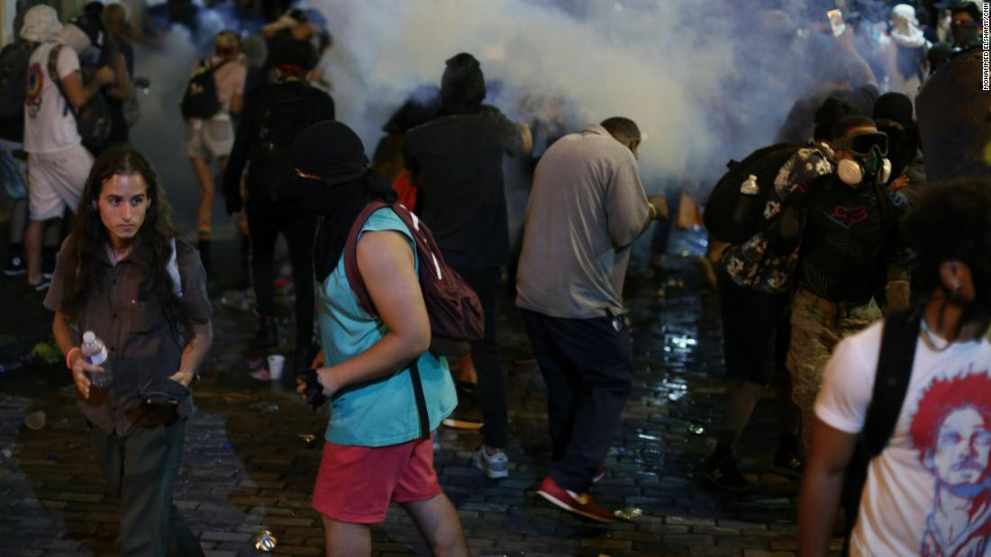 Protesters disperse in a cloud of tear gas.