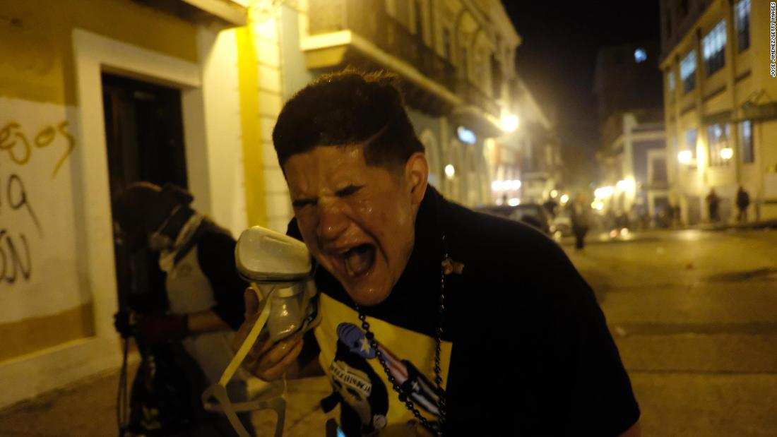 A protester reacts to tear gas outside the governor's mansion.