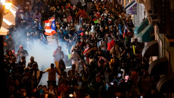 Protesters run away from tear gas near the governor's mansion.