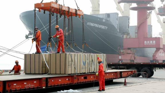 LIANYUNGANG, CHINA - JULY 15: Workers load boxes of Melamine Faced MDF onto a ship at Lianyungang Port on July 15, 2019 in Lianyungang, Jiangsu Province of China. China's GDP expanded 6.3 percent year-on-year in the first half of this year, according to the National Bureau of Statistics on Monday. (Photo by Wang Chun/VCG via Getty Images)