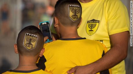 "Supporters of Israeli football club Beitar Jerusalem enter the stadium bearing the club's shield on their heads prior to their return match against Belgium team Charleroi on July 23, 2015 at Teddy Stadium in Jerusalem. Beitar Jerusalem owner Eli Tabib announced after the first leg of Europa League match between Charleroi and Beitar was halted in Belgium that he was ""ashamed"" by the conduct of an ""extremist group of fans"" and intended to sell the team. AFP PHOTO / MENAHEM KAHANA        (Photo credit should read MENAHEM KAHANA/AFP/Getty Images)"
