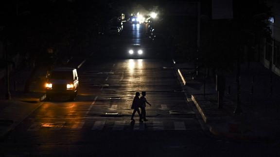 People crossing a street in Caracas on July 22, 2019 as the capital and other parts of Venezuela are being hit by a massive power cut.