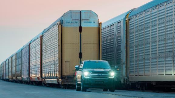 An electric Ford F-150 tows train cars.
