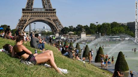 On Tuesday, people bask in the Trocadero fountain in Paris and cool off.