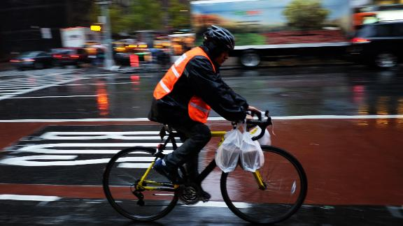 A delivery man rides his bike in the rain to deliver food in New York on November 17, 2014. The coldest air since last winter is set to move into the East during the first few days of the week, with high temperatures from Washington, DC, through New York City forecast to stay near or below freezing 32F (0C) on Tuesday, levels that would be considered below normal even during the heart of winter. AFP PHOTO/Jewel Samad        (Photo credit should read JEWEL SAMAD/AFP/Getty Images)