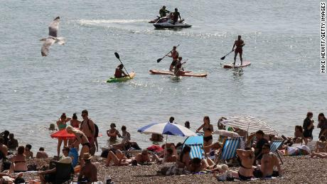 Many flocked to the beach on Tuesday to cool off in Brighton, southern England.