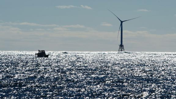 A boat passes one of the wind turbines of the Block Island Wind Farm on October 14, 2016 off the shores of Block Island, Rhode Island. The first offshore wind project in America has created more than 300 construction jobs and will deliver the electricity demands for the entire island.  / AFP / DON EMMERT        (Photo credit should read DON EMMERT/AFP/Getty Images)