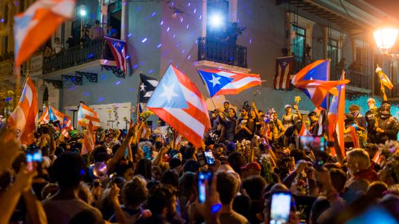 People celebrate outside the governor's mansion La Fortaleza, after Gov. Ricardo Rossello announced that he is resigning Aug. 2 after nearly two weeks of protests and political upheaval touched off by a leak of crude and insulting chat messages between him and his top advisers, in San Juan, Puerto Rico, Thursday, July 25, 2019. (AP Photo/Dennis M. Rivera Pichardo)