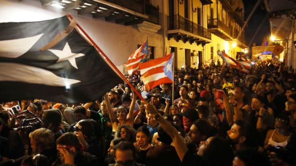 Puerto Ricans wave flags in celebration of Rosselló's resignation.