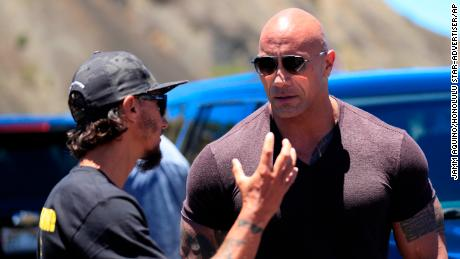 "Actor Dwayne ""The Rock"" Johnson, right, talks with TMT opposition leader Kaho'okahi Kanuha during a visit to the protests against the TMT telescope, Wednesday, July 24, 2019, at the base of Mauna Kea on Hawaii Island. (Jamm Aquino/Honolulu Star-Advertiser via AP)"