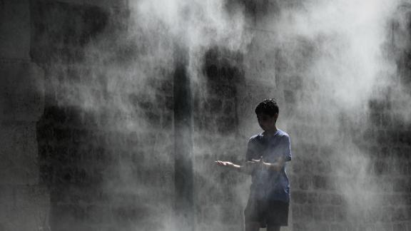 TOPSHOT - A boy cools off under a public water spray on the bank of the Seine river in Paris on July 25, 2019 as a new heatwave hits Europe. - After all-time temperature records were smashed in Belgium, Germany and the Netherlands on July 24, Britain and the French capital Paris could on July 25 to see their highest ever temperatures (Photo by Philippe LOPEZ / AFP)        (Photo credit should read PHILIPPE LOPEZ/AFP/Getty Images)