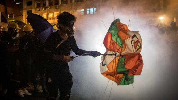 """HONG KONG, HONG KONG - JULY 21: Protesters clash with police amid tear gas after taking part in an anti-extradition bill march on July 21, 2019 in Hong Kong, China. Pro-democracy protesters have continued weekly rallies on the streets of Hong Kong against a controversial extradition bill since  June 9, as the city plunged into crisis after waves of demonstrations and several violent clashes. Hong Kong's Chief Executive Carrie Lam apologized for introducing the bill and recently declared it """"dead"""", however protesters have continued to draw large crowds with demands for Lam's resignation and completely withdraw the bill. (Photo by Chris McGrath/Getty Images)"""
