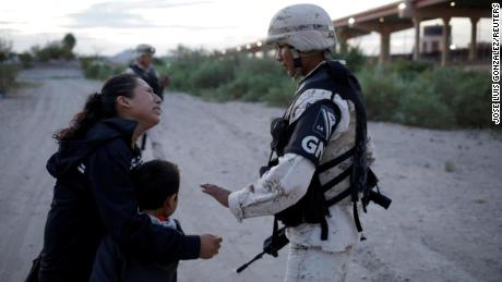 Lety Perez embraces her son, Anthony, while asking a member of the Mexican National Guard to let them cross into the United States.
