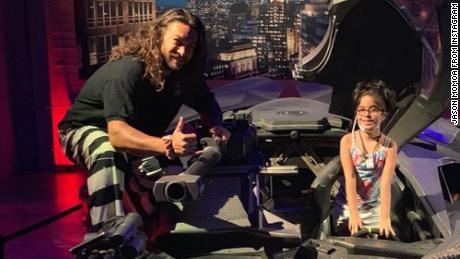 Jason Momoa and a young fan hop into the Batmobile.