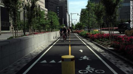 A group of cyclists ride along a dedicated bike lane in downtown Manhattan in New York.