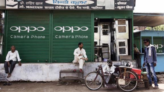 People rest outside a shuttered store displaying an advertisement for smartphone maker Oppo Electronics Corp. in Gwalior, Madhya Pradesh, India, on Friday, June 2, 2017. India