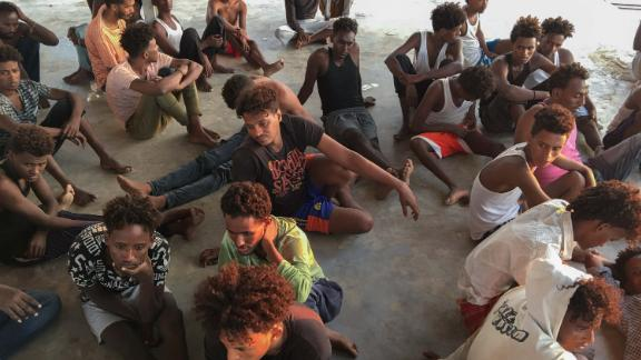 Rescued migrants sit on a coast some 100 kilometers east of Tripoli, Libya, Thursday.