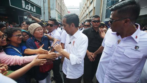 Indonesian President Joko Widodo greets people at the Pasar Baroe shopping center in central Jakarta.