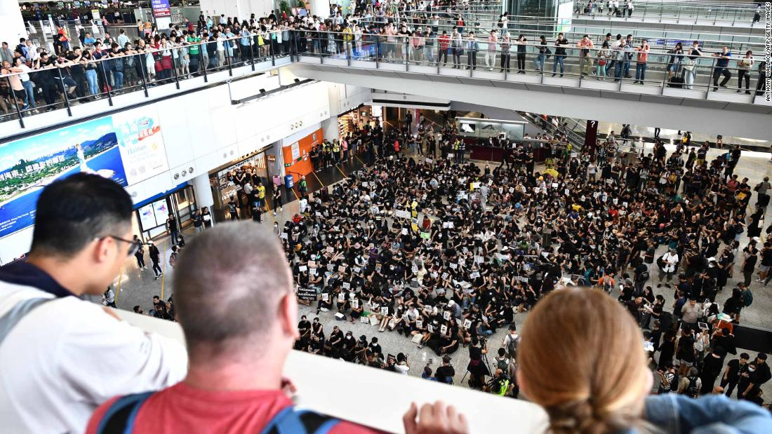 Travelers watch as protesters rally against a controversial extradition bill at the international airport in Hong Kong on Friday, July 26.