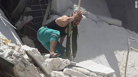 Father watches as daughters dangle from airstrike debris.