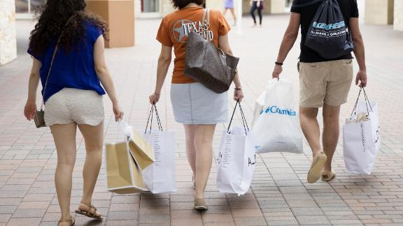 Pedestrians carry shopping bags while walking through the Grand Prairie Premium Outlets mall in Grand Prairie, Texas, U.S., on Monday, May 23, 2016. The Bloomberg Consumer Comfort Index, a survey which measures attitudes about the economy, is scheduled to be released on May 26. Photographer: Laura Buckman/Bloomberg via Getty Images