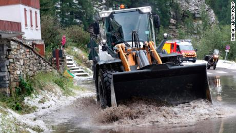 A worker uses a digger to clean the road during the 19th stage of the Tour de France. Race organizers stopped the race because of a hail storm as Julien Alaphilippe lost his yellow jersey to Egan Bernal.