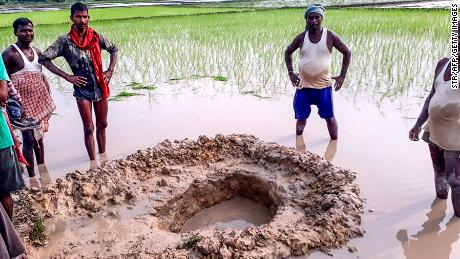Villagers and farmers pose around the crater of a suspected meteorite that crashed in a field at Mahadeva village in the Indian eastern state of Bihar.