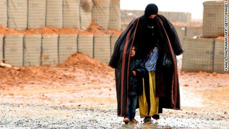 A Syrian refugee from the informal Rukban camp, which lies in no-man's-land off the border between Syria and Jordan in the remote northeast, walks in the rain.